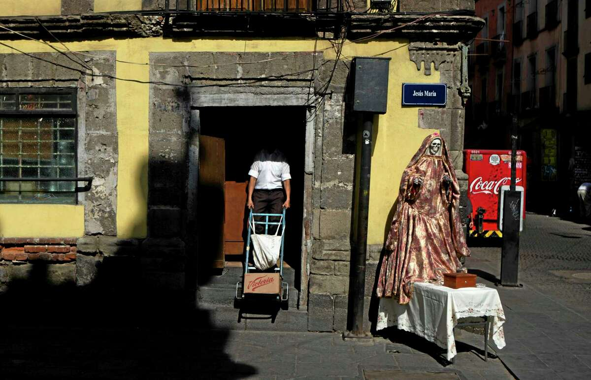 """A statue of La Santa Muerte, or Holy Death, stands on a street corner in the historic center of Mexico City May 5. La Santa Muerte is depicted as a smiling female skeleton and is known as our """"Our Little White Girl,"""" the right-hand servant of God."""