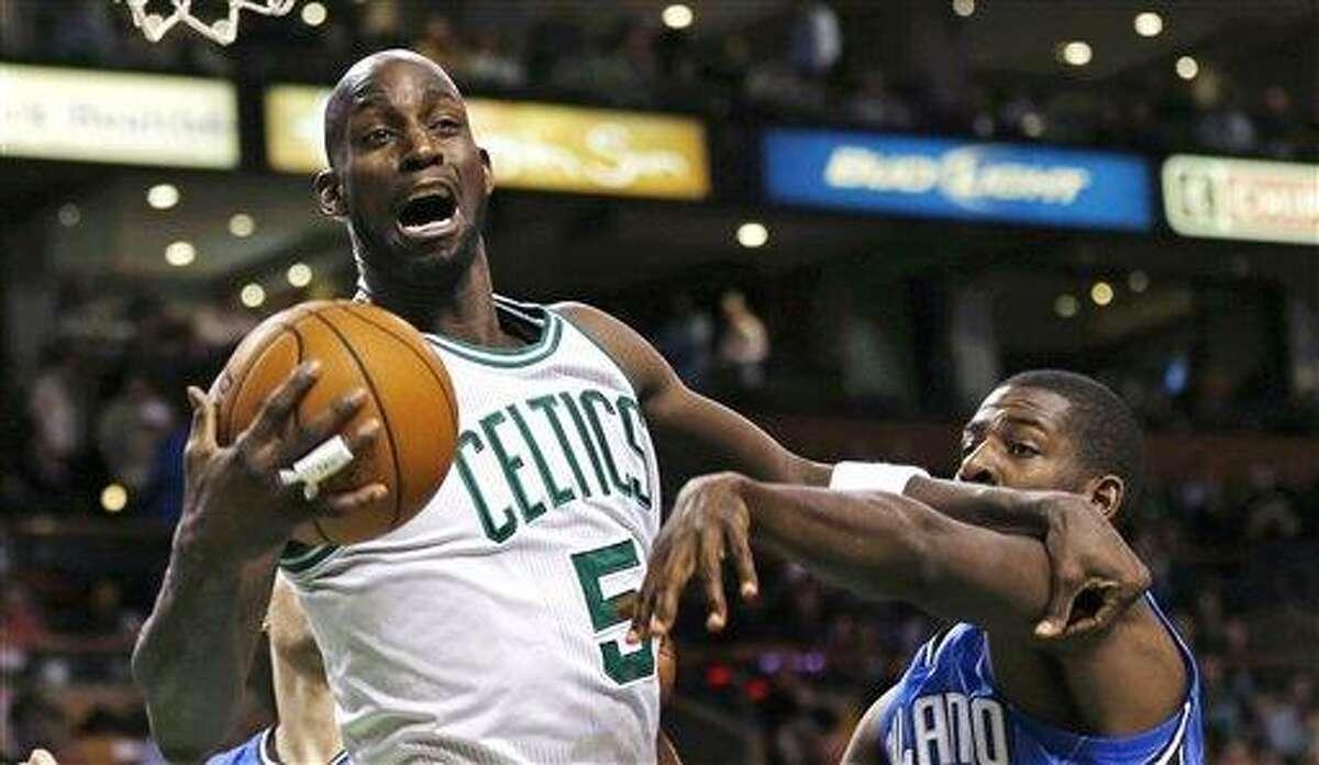 Boston Celtics forward Kevin Garnett (5) grabs a rebound against Orlando Magic forward Andrew Nicholson (44) during the first quarter of an NBA basketball game in Boston, Friday, Feb. 1, 2013. (AP Photo/Charles Krupa)