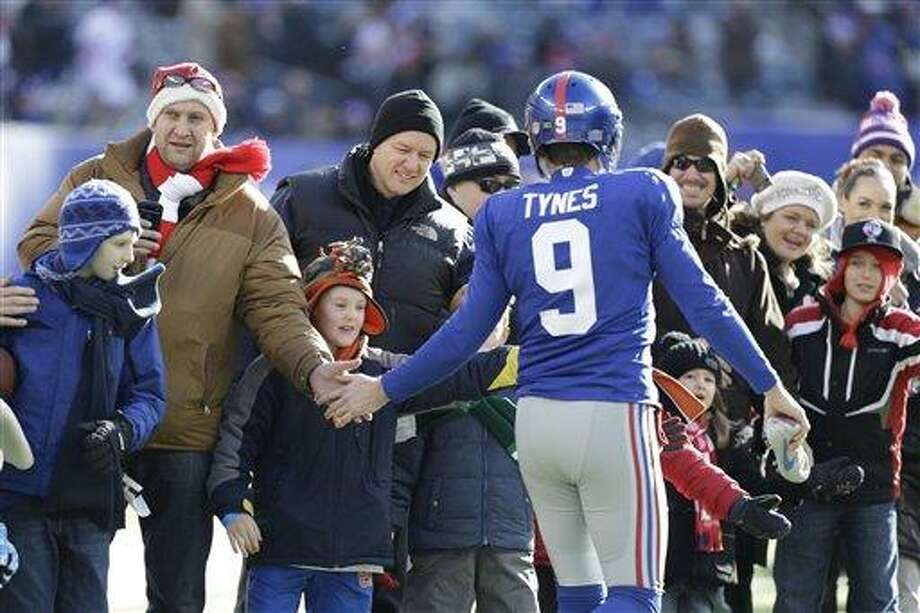 The Knicks aren't the only sports team to remember Sandy Hook elementary School folks. In this Dec. 30, 2012, file photo, New York Giants kicker Lawrence Tynes (9) greets a contingent of teachers, parents, and students from Sandy Hook Elementary School in Newtown, Conn., before an NFL football game in East Rutherford, N.J. Since the Sandy Hook Elementary School shooting tragedy on Dec. 14, 2012, athletes from across the sports world have done their part to help make Newtown children smile again. (AP Photo/Kathy Willens, File) Photo: AP / AP
