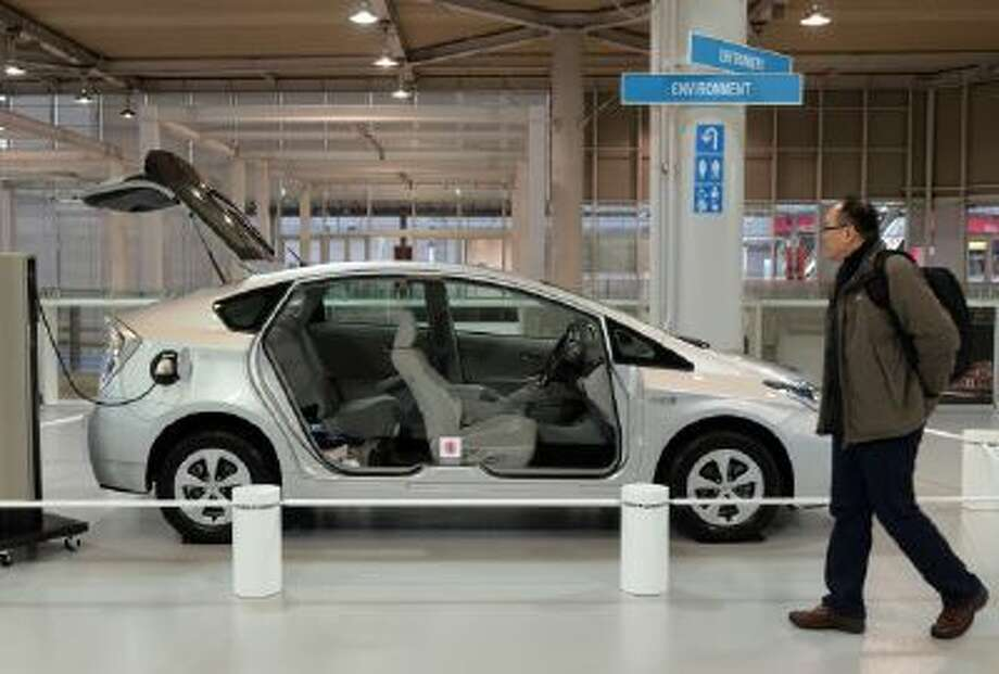 A customer checks a cut model of Prius plug-in hybrid vehicle (PHV) of Japanese auto giant Toyota Motor at the company's showroom in Tokyo on January 15, 2014.