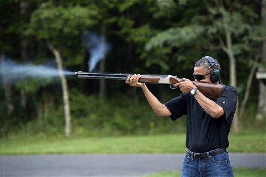 """In this photo released by the White House, President Barack Obama shoots clay targets on the range at Camp David, Md., Saturday, Aug. 4, 2012. The White House released a photo of Obama firing a gun, two days before he heads to Minnesota to discuss gun control. In a recent interview with The New Republic magazine, Obama said yes when asked if he has ever fired a gun. He said """"we do skeet shooting all the time,"""" except for his daughters, at Camp David. (AP Photo/The White House, Pete Souza) Photo: AP / The White House"""