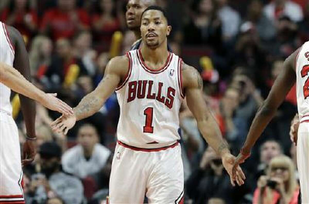 Chicago Bulls guard Derrick Rose (1) celebrates with teammates after scoring a free-throw shot during the second half of an NBA preseason basketball game against the Indiana Pacers in Chicago on Friday, Oct. 18, 2013. the Bulls won 103-98. (AP Photo/Nam Y. Huh)