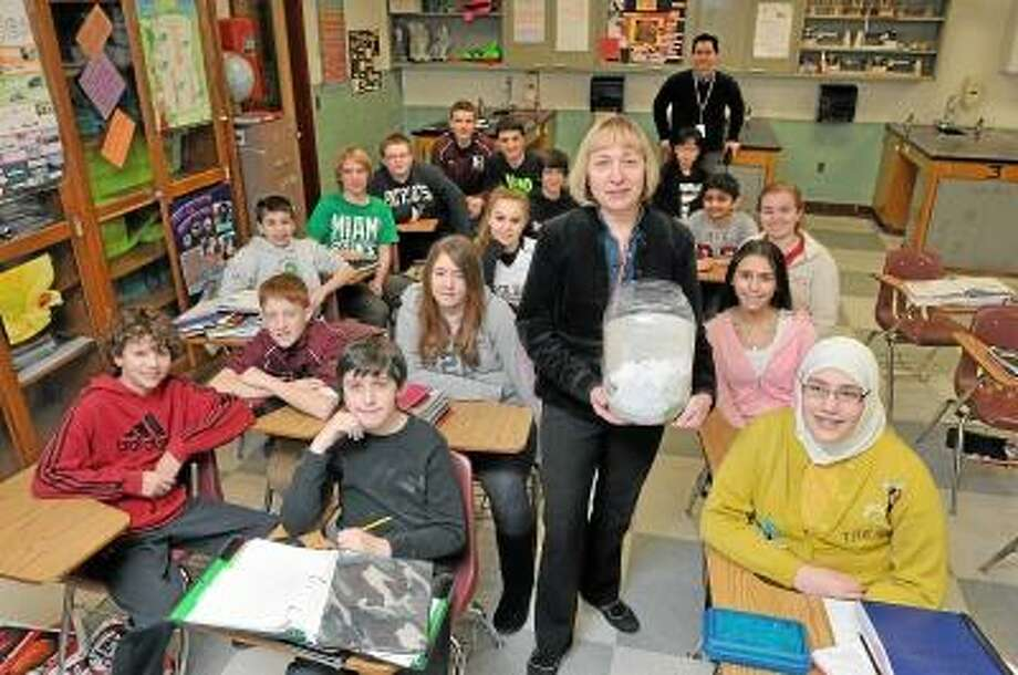 """North Haven Middle School science teacher Clara Laster, with her students are participating in """"26 Acts of Kindness"""" at the school. She is holding a jug containing some of the notes describing each act that the students have done so far. The 26 acts of kindness represent the victims of the Sandy Hook shootings. Photo-Peter Casolino"""