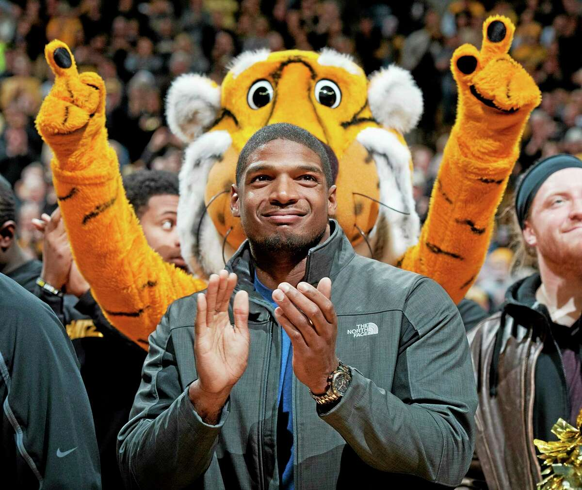 In this Feb. 15 file photo, Missouri's All-American defensive end Michael Sam claps during the Cotton Bowl trophy presentation at halftime of a college basketball game between Missouri and Tennessee in Columbia, Mo. Sam has been selected the winner of the Arthur Ashe Courage Award. The Missouri defensive end who likely will be drafted by an NFL team this weekend, will receive the award given to individuals who transcend sports at The ESPYs on July 16.
