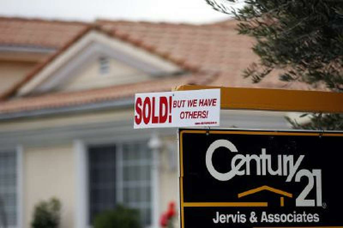 A real estate sign is seen outside a home in Downey, Calif., Wednesday, Jan. 23, 2013.