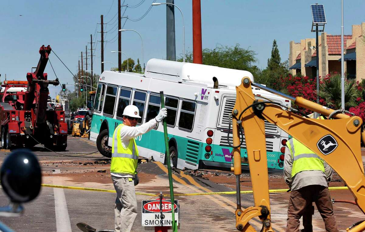 A valley metro bus sits mired in a collapsed, muddy street after a water main break flooded the area, Wednesday, Sept. 3, 2014 in Tempe, Ariz.