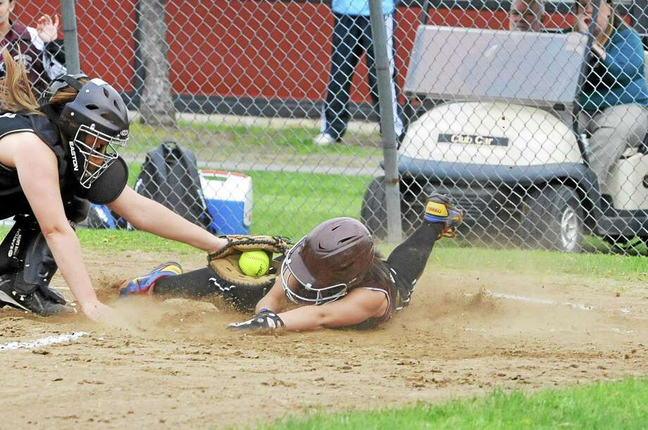 Torrington's Alexis Tyrrell slides safely into home plate, beating Woodland's Rachel Starkey's tag, to score the Red Raiders first run of the game in their 4-0 win against the Hawks. Photo: Laurie Gaboardi — Register Citizen