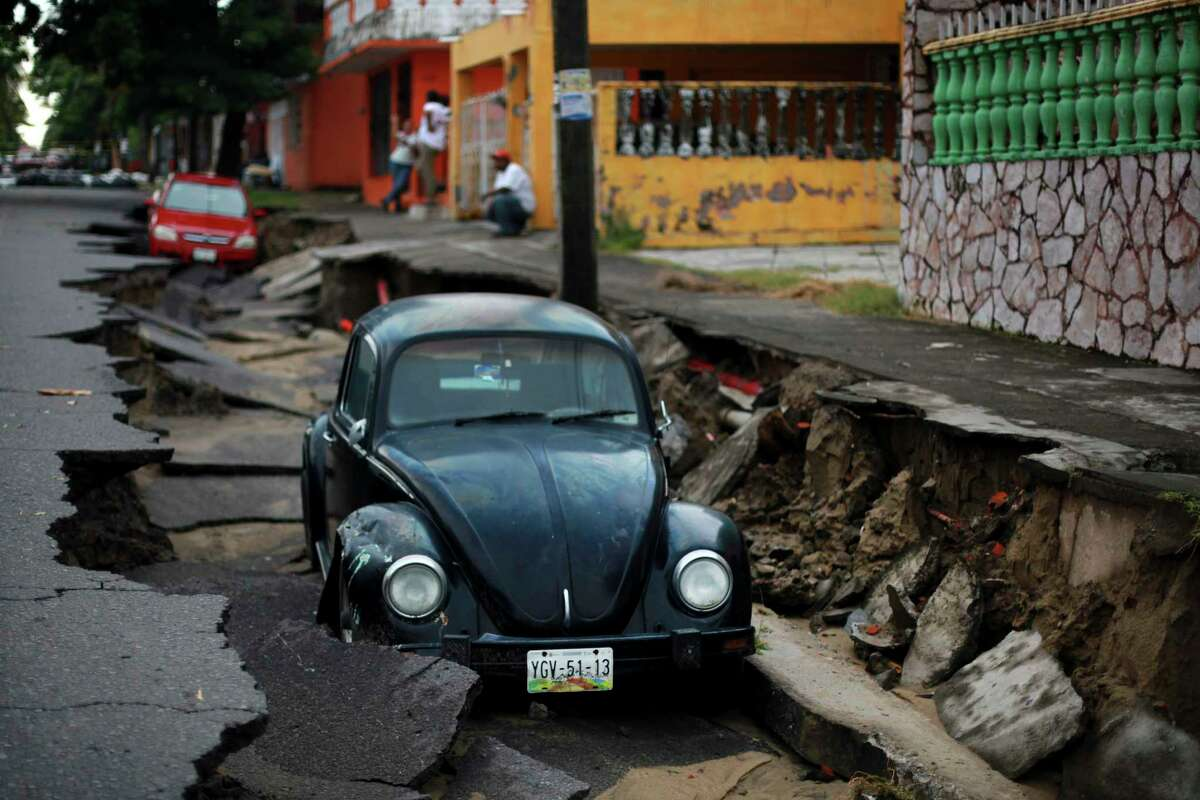 Cars sit on a street that collapsed after heavy rain in the Gulf port city of Veracruz, Mexico, Tuesday, Sept. 2, 2014. The Gulf states of Mexico are bracing for more bad weather as Tropical Storm Dolly crosses the coast and continues moving inland over northeastern Mexico on Wednesday.
