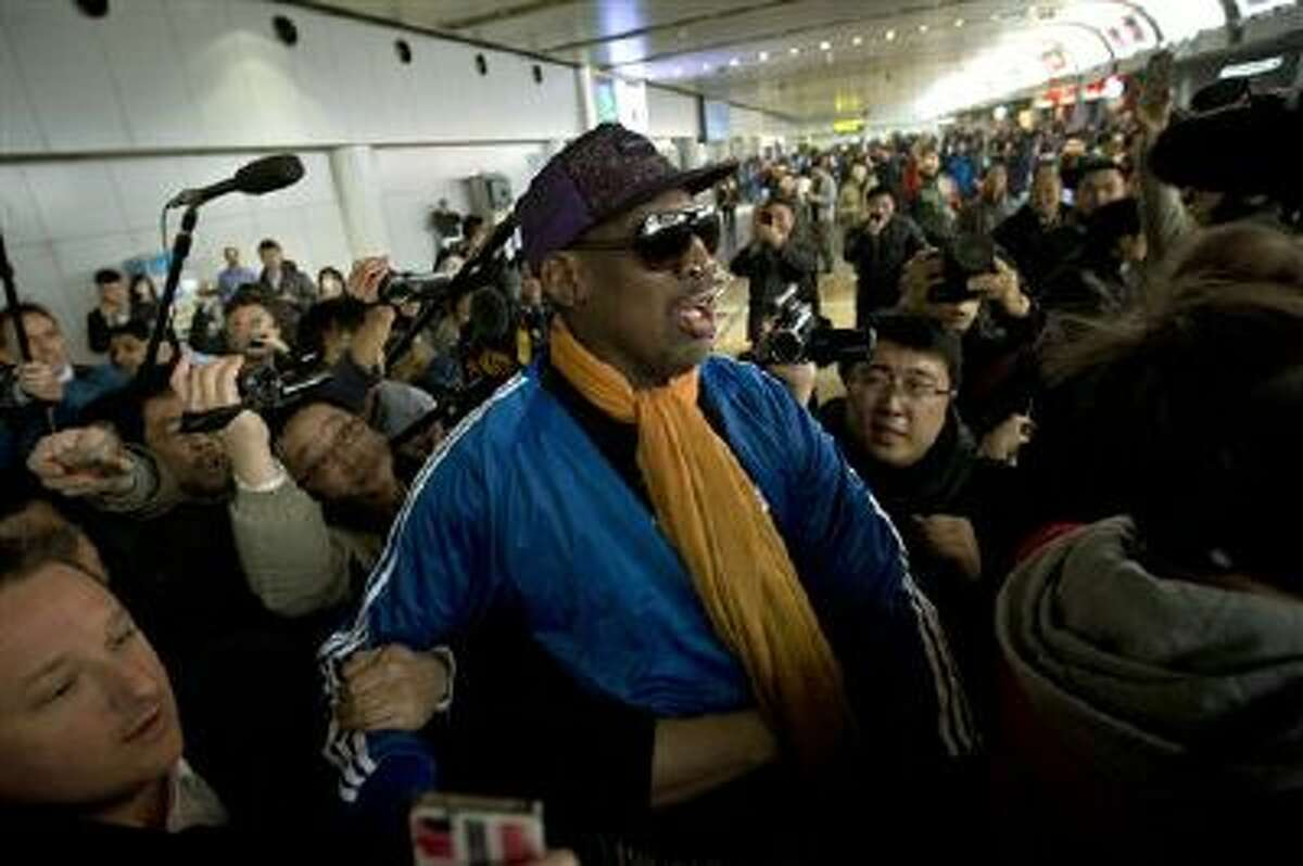 Former NBA basketball player Dennis Rodman is followed by journalists Jan. 13 as he arrives at the Capital International Airport in Beijing from Pyongyang.
