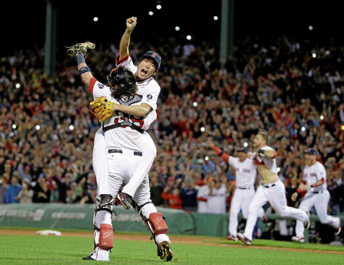Red Sox relief pitcher Koji Uehara, rear, and catcher Jarrod Saltalamacchia celebrate Boston's 5-2 win over the Detroit Tigers in Game 6 of the ALCS on Saturday.