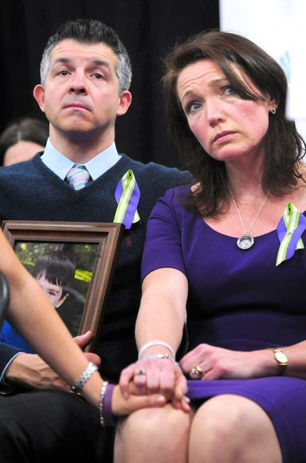 Ian Hockley (left) holding a photograph of his son, Dylan, and his wife, Nicole (right), listen to speakers a press conference announcing the launch of Sandy Hook Promise at Edmond Town Hall in Newtown on 1/14/2013.  Dylan was killed in the Sandy Hook Elementary School shootings.Photo by Arnold Gold/New Haven Register