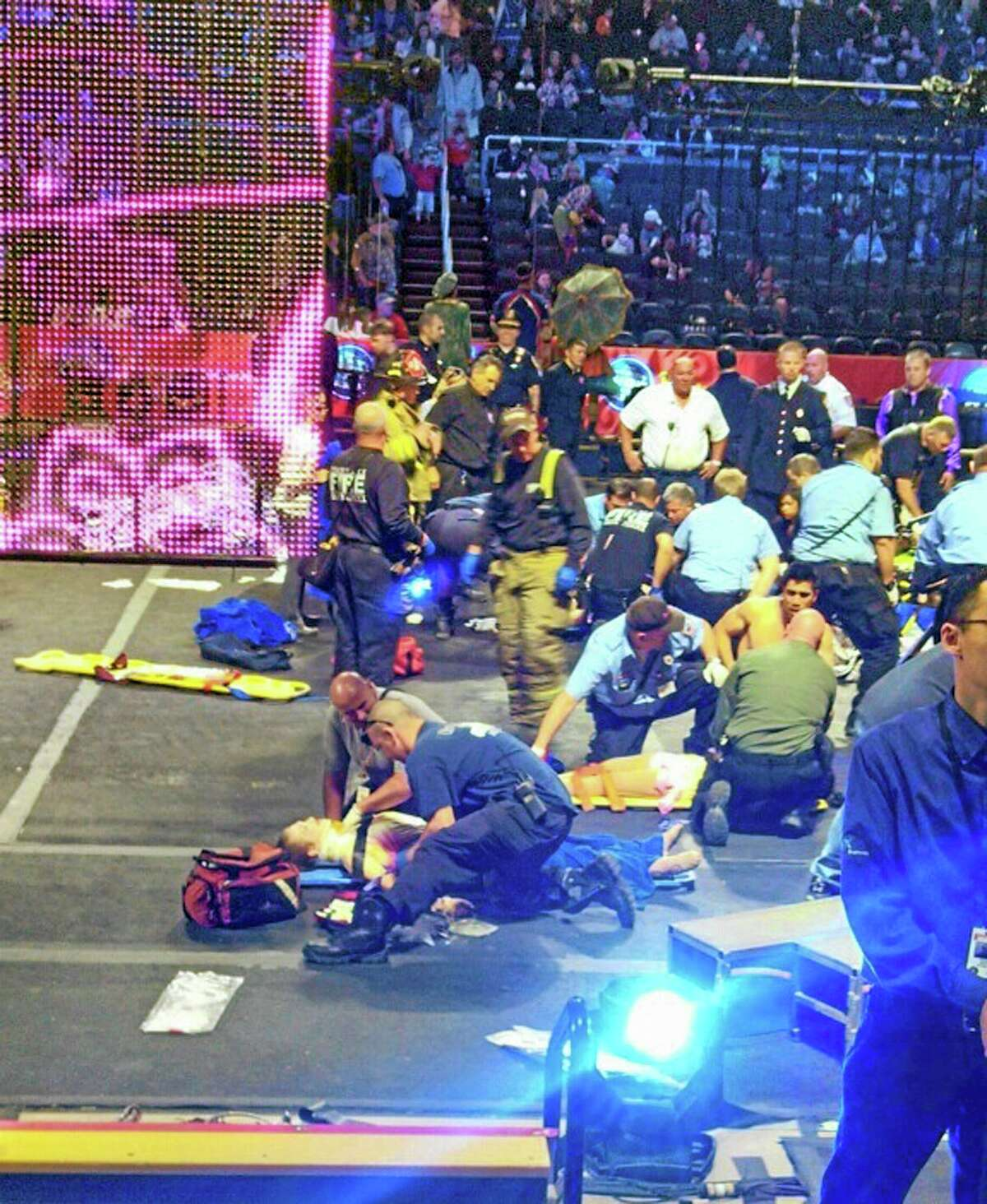 In this photo provided by Rosa Viveiros, first responders work at the center ring after a platform collapsed during an aerial hair-hanging stunt at the Ringling Brothers and Barnum and Bailey Circus, Sunday, May 4, 2014, in Providence, R.I. At least nine performers were seriously injured in the fall, including a dancer below, while an unknown number of others suffered minor injuries. (AP Photo/Rosa Viveiros) MANDATORY CREDIT