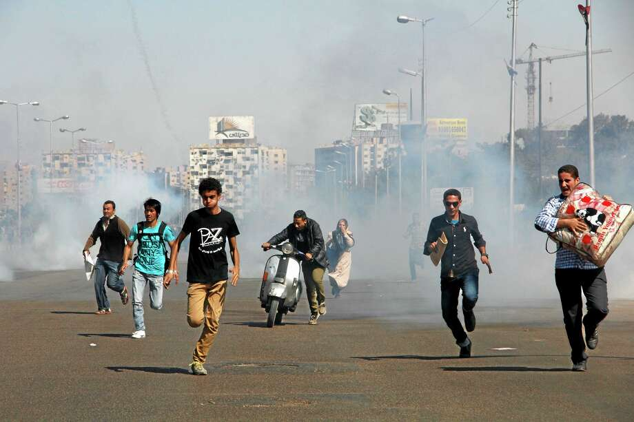 Egyptians run from tear gas after clashes erupted between Al-Azhar students and police forces during a protest in the Nasr City district of Cairo, Sunday, Oct. 20, 2013. The protests were the second in two days at Al-Azhar University, Sunni Islam's most prominent center of learning. Many supporters of ousted Egyptian President Mohammed Morsi's Muslim Brotherhood group are students at Al-Azhar, a stronghold of the group and steps from former site of an Islamists' sprawling protest camp which came under heavy crackdown by security forces on Aug. 14, leaving hundreds dead and sparking days of unrest and violence across the country. (AP Photo/Heba el-Kholy, El Shorouk Newspaper) EGYPT OUT Photo: AP / El Shorouk Newspaper