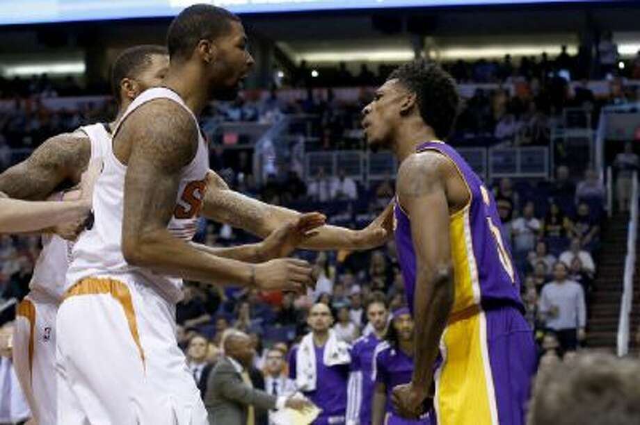 Nick Young, right, has words with Phoenix Suns' Marcus Morris and Markieff Morris, rear, during the first half.