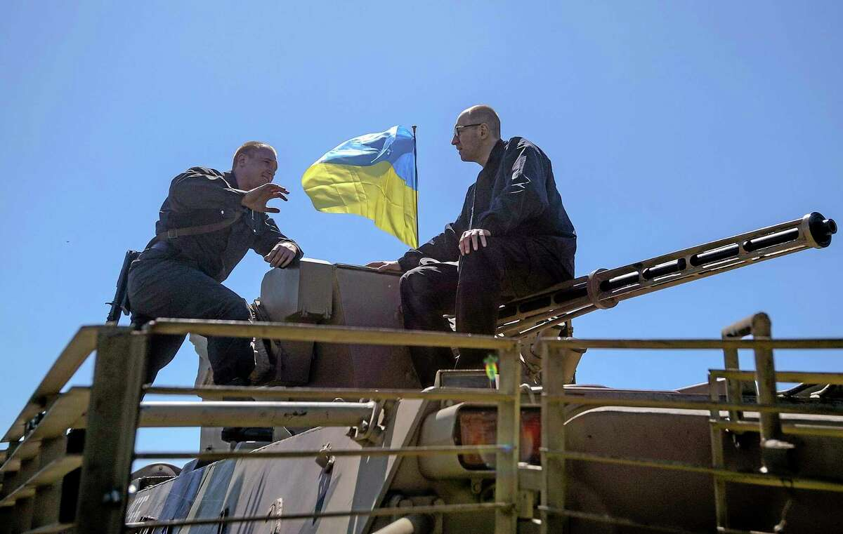 Ukrainian Prime Minister Arseniy Yatsenyuk, right, sits on top of an APC as he speak with a Ukrainian soldier at a block post on the road at Slovyansk, Ukraine, Wednesday, May 7, 2014. Ukrainian military operations that began Monday to expunge pro-Russia forces from the city of Slovyansk were the interim government's most ambitious effort so far to quell weeks of unrest in Ukraine's mainly Russian-speaking east. (AP Photo/Andrew Kravchenko, Pool)