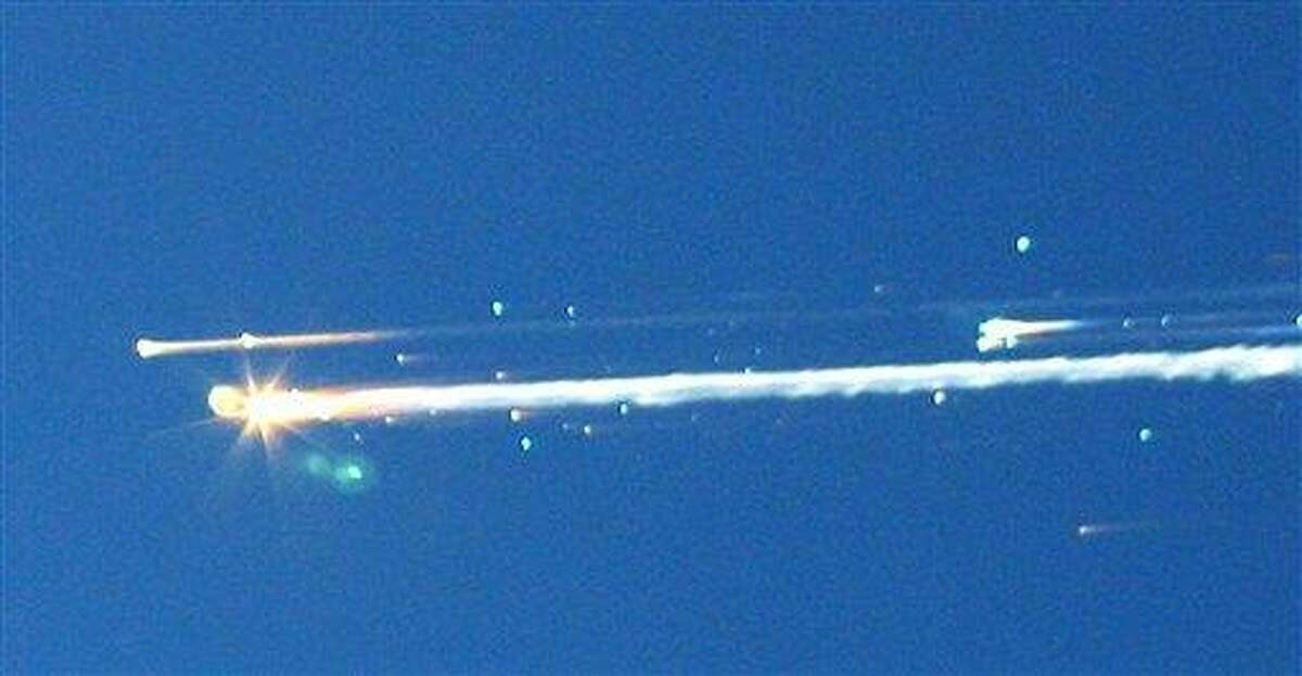 """In this Feb. 1, 2003, file photo, debris from the space shuttle Columbia streaks across the sky over Tyler, Texas. The Columbia broke apart in flames 200,000 feet over Texas, killing all seven astronauts just minutes before they were to glide to a landing in Florida. Ten years later, reminders of Columbia are everywhere, including up in the sky. Everything from asteroids, lunar craters and Martian hills, to schools, parks, streets and even an airport (Rick Husband Amarillo International Airport) bear the Columbia astronauts' names. Two years ago, a museum opened in Hemphill, Texas, where much of the Columbia wreckage rained down, dedicated to """"remembering Columbia."""" About 84,000 pounds of that wreckage, representing 40 percent of NASA's oldest space shuttle, are stored at Kennedy and loaned for engineering research. (AP Photo/Scott Lieberman) MANDATORY CREDIT"""