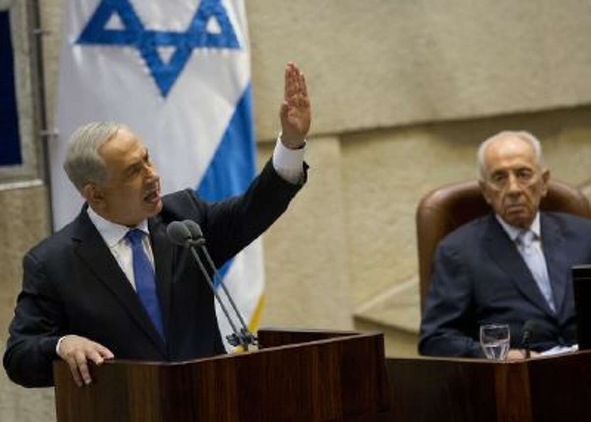Israel's President Shimon Peres, right, listens to Prime Minister Benjamin Netanyahu speech during the opening session of the Knesset, Israel's parliament, in Jerusalem, Monday, Oct. 14, 2013.