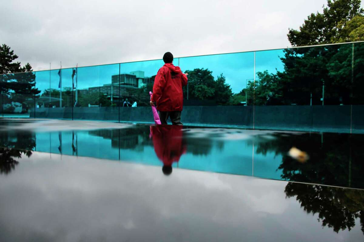 A woman passes the new monument for the victims of euthanasia Berlin, Tuesday, Sept. 2, 2014. Germany has inaugurated the memorial to more than 200,000 people with physical and mental disabilities who were killed by the Nazis, who deemed their lives ìworthless. The 24-meter (79-foot) blue glass pane stands on the site of a villa where the mass murder of patients at hospitals and mental institutes was coordinated starting in 1940. The euthanasia programís methods included using gas chambers. (AP Photo/Markus Schreiber)
