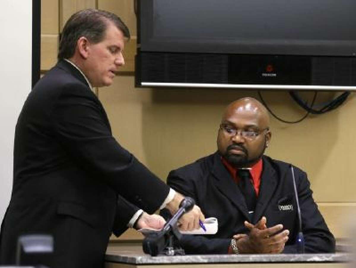 Prosecutor Gregg Rossman, left, shows witness Dwayne Nicholson a document during Nicholson's testimony, Thursday, Oct. 3, 2013, in Fort Lauderdale, Fla.