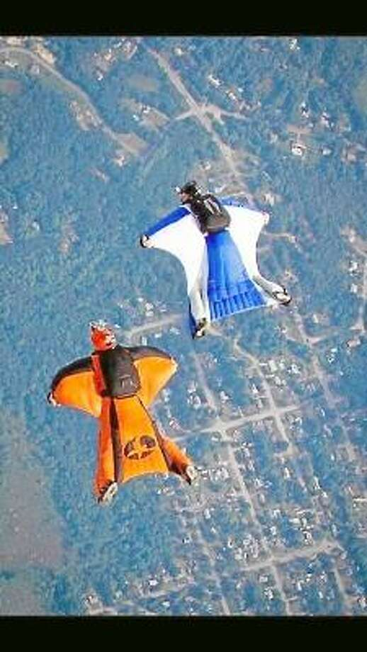 Torrington residents Ariel Lagasa (left) and Jason Bresson (right) survey the landscape as they fly through the air in their wing suits. Submitted Photo.