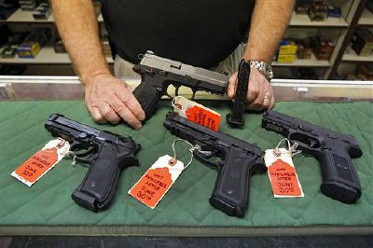 A store manager in Aurora, Colo., shows some of the pistols that he won't be able to sell under new gun laws in Colorado because their magazines hold more than 15 rounds.
