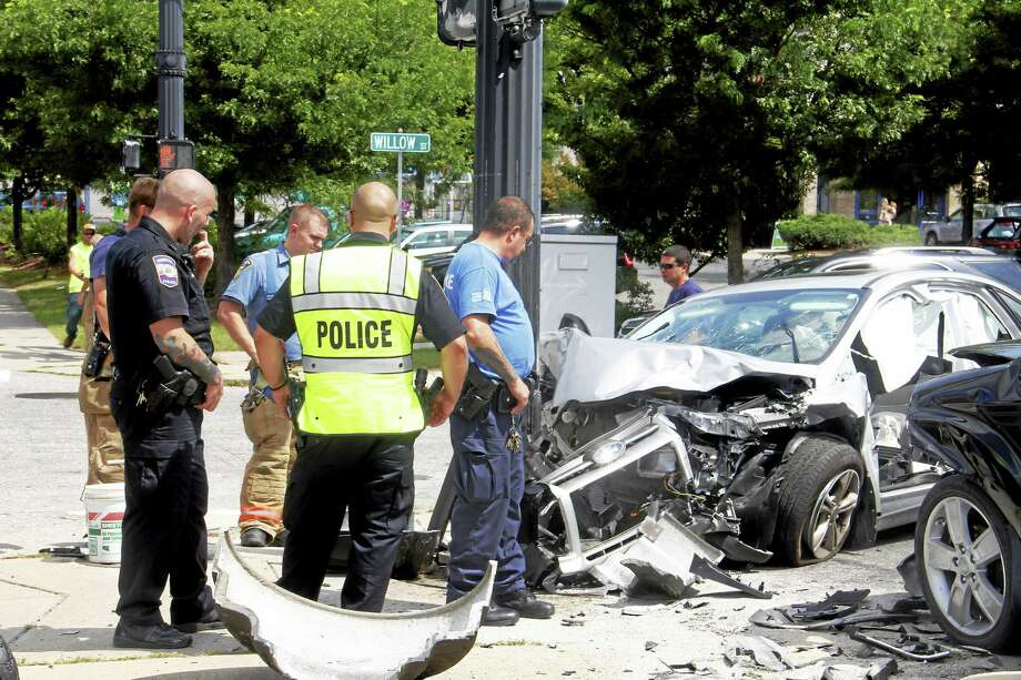 Officials examine the wreckage of a car that struck a traffic light pole on East Main Street on Tuesday, Sept. 2, in Torrington. The driver of the car required hospitalization but was conscious when taken to Waterbury Hospital, officials on scene said. Photo: Esteban L. Hernandez — Register Citizen