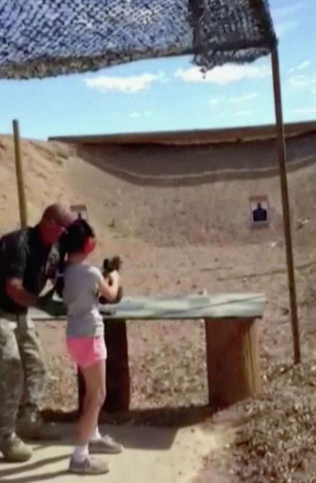 In this Aug. 25 image made from video and provided by the Mohave County Sheriff Department, firing-range instructor Charles Vacca, left, shows a 9-year-old girl how to use an Uzi. Vacca, 39, was standing next to the girl at the Last Stop range in Arizona, south of Las Vegas, when the girl squeezed the trigger, causing the Uzi to recoil upward and shoot Vacca in the head.
