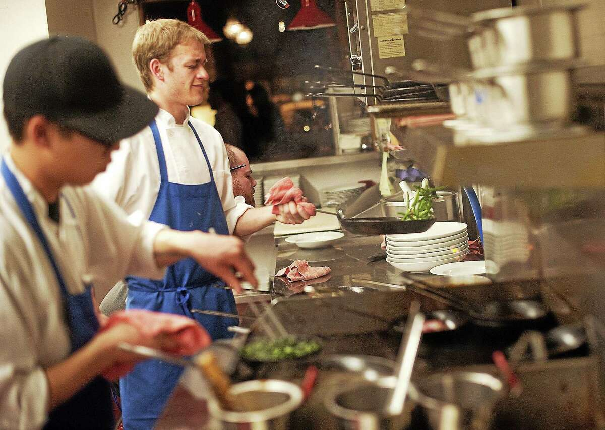 Chefs Marcus Eng, left, and Spencer Caine, center, cook in the kitchen at Twelve Restaurant in Denver on a busy Friday night in February 2013.