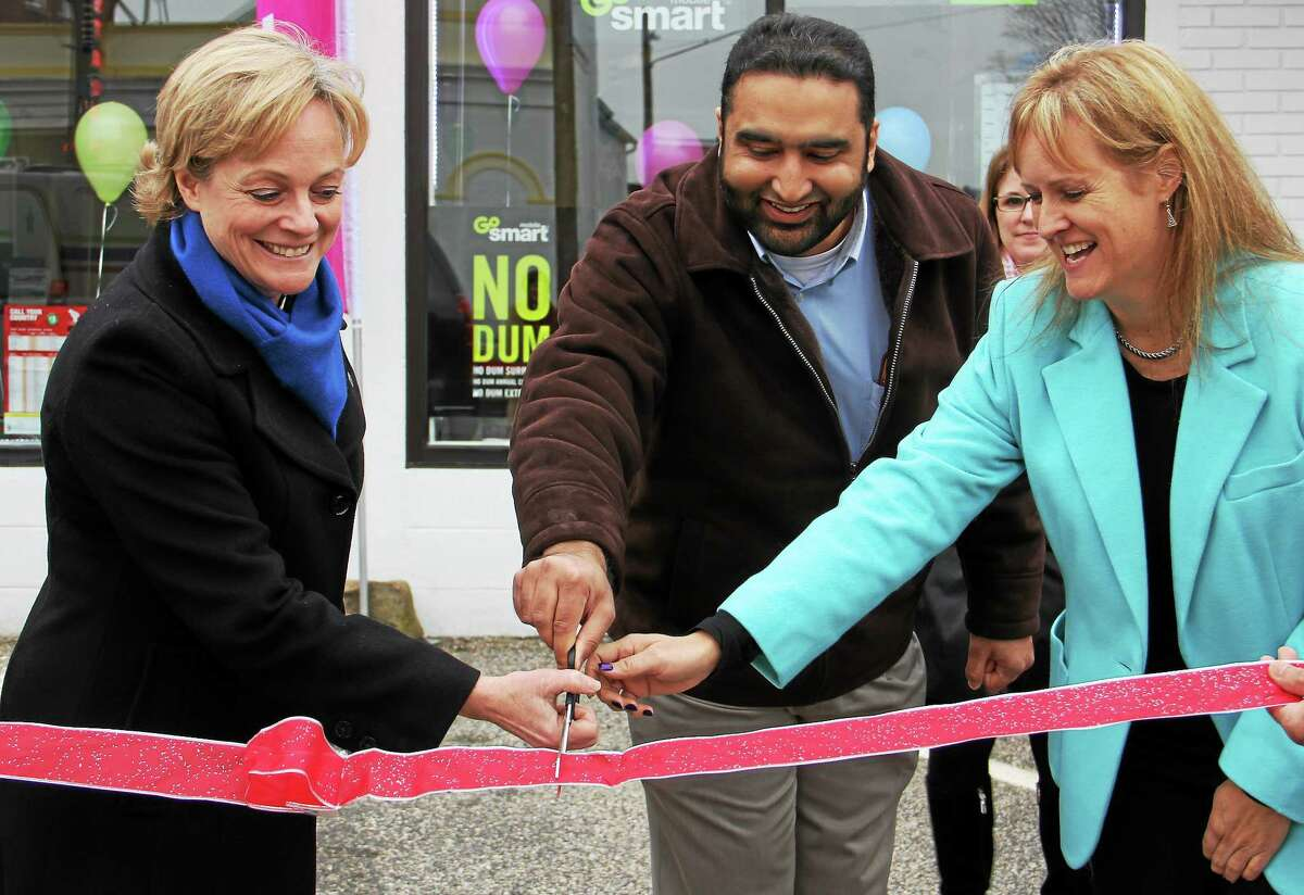 (From left) Torrington Mayor Elinor Carbone, Tarar Wireless president Osman Tarar and Liberty Tax Service owner and manager Kristin Kicza smile as they cut a ribbon to commemorate their store's grand opening on Thursday, Jan. 16, 2014, in Torrington. The two businesses are located inside the same building and decided to hold a joint grand opening.