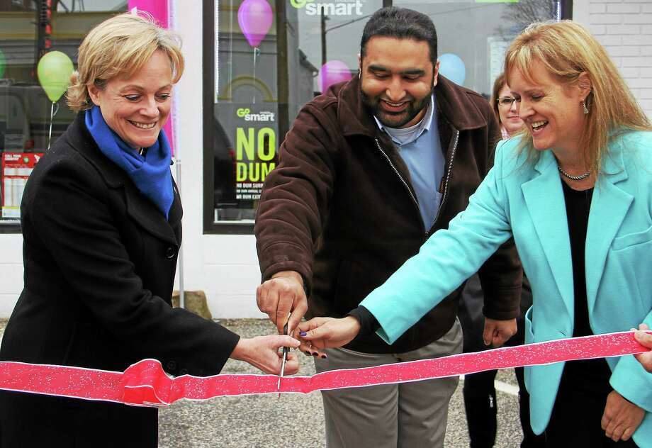 (From left) Torrington Mayor Elinor Carbone, Tarar Wireless president Osman Tarar and Liberty Tax Service owner and manager Kristin Kicza smile as they cut a ribbon to commemorate their store's grand opening on Thursday, Jan. 16, 2014, in Torrington. The two businesses are located inside the same building and decided to hold a joint grand opening. Photo: Esteban L. Hernandez — Register Citizen