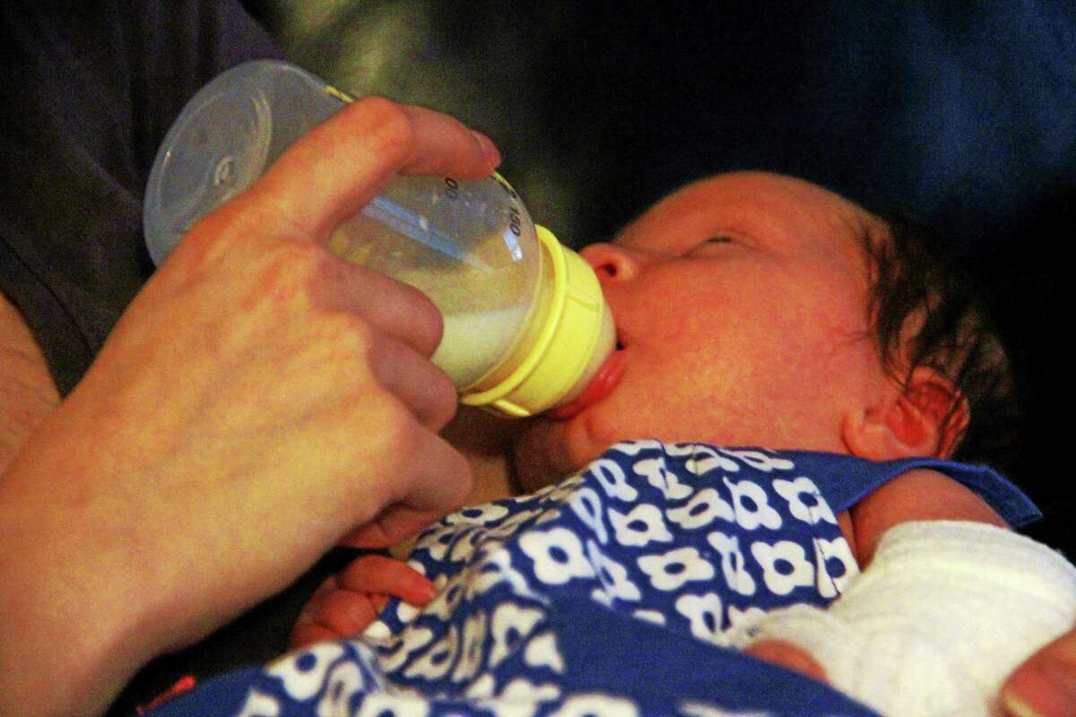 Zoe Fortier nurses from a bottle in her mother's arms on Aug. 29, in Torrington. The 1-month old girl has a rare disorder that makes her bones fragile and prone to injury.