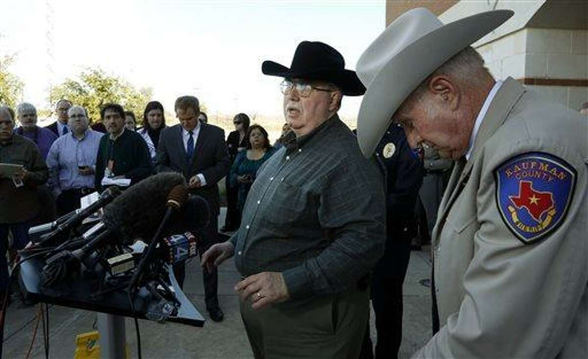 This Jan. 31, 2013 file photo shows David Byrnes, Sheriff of Kaufman County, right, bowing his head as Mike McLelland, District Attorney of Kaufman County answers questions at a news conference at the Kaufman Law Enforcement Center in Kaufman, Texas. McLelland and his wife where found dead in their home Saturday March 30, 2013. Authorities are investigating. (AP Photo/The Dallas Morning News, David Woo, File )