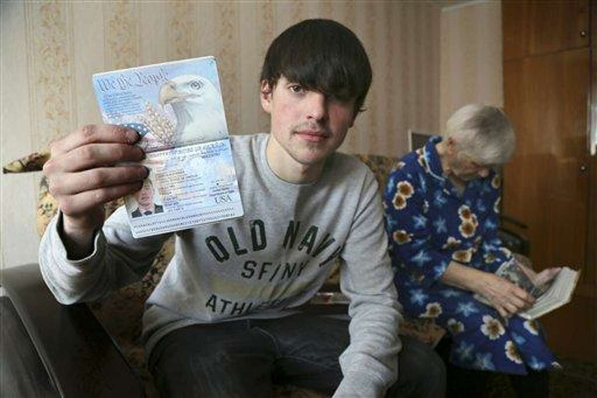 In this photo taken on Saturday, March 20, 2013, Alexander Abnosov shows his American passport to journalists in the Volga river city of Cheboksary, Russia. His 72 -years old grandmother is in the background. Abnosov was adopted by an American couple at age 12 has returned to Russia claiming that his parents treated him badly, according to reports from Russian media with close ties to the Kremlin. (AP Photo/Nikolay Alexandrov)