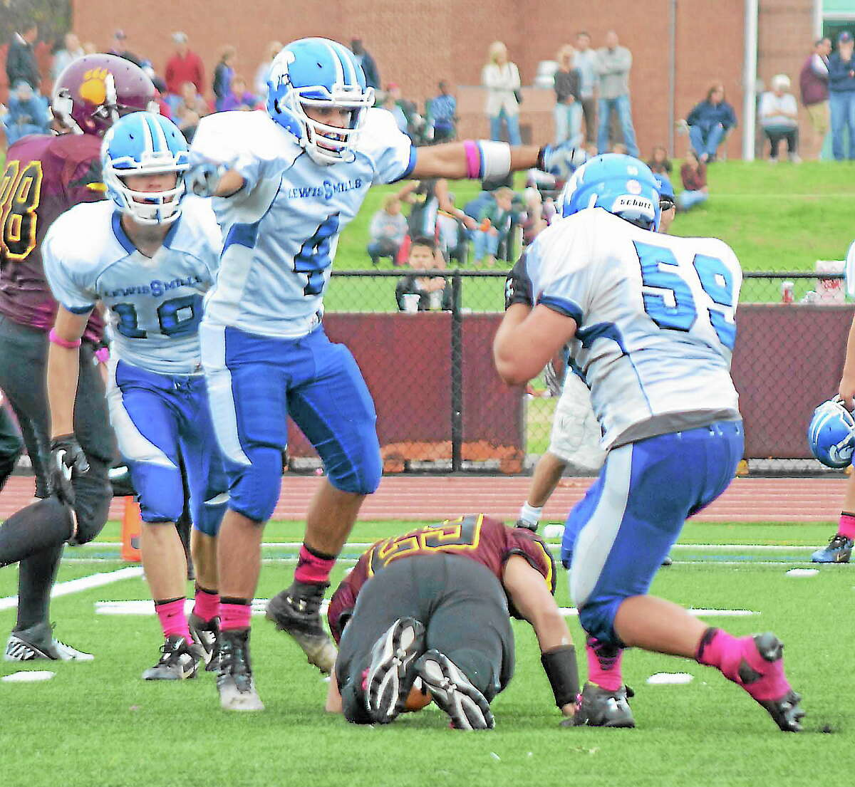 Lewis Mills' Aris Artemiadis (4) and Cameron McHale (59) celebrate after McHale tackled Granby's Anthony LaTorre (29) for a loss.