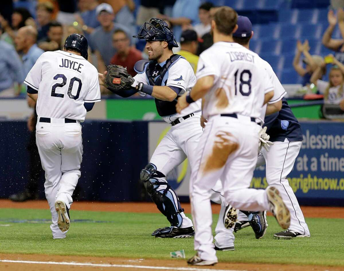 Tampa Bay Rays players chase Matt Joyce after his walk-off hit off Boston Red Sox reliever Burke Badenhop in the 10th inning Monday in St. Petersburg, Fla.