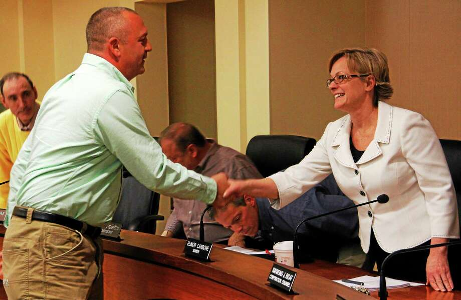 Fire Department Lt. Patrick Doyle shakes hands with Mayor Elinor Carbone after his promotion to Captain Wednesday during a Board of Public Safety meeting in Torrington. Doyle was one of three firefighters granted a promotion during the meeting. Photo: Esteban L. Hernandez — Register Citizen