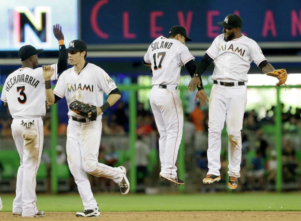 Shortstop Adeiny Hechavarria (3), left fielder Christian Yelich, second from left, second baseman Donovan Solano (17) and center fielder Marcell Ozuna celebrate after the Marlins defeated the New York Mets 9-6 on Monday in Miami.