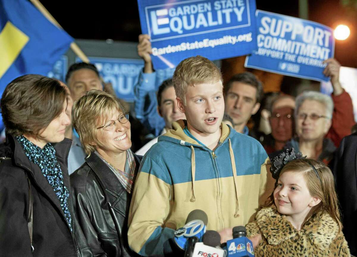 Karen Nicholson-McFadden,left, and Marcye Nicholson-McFadden,center, of Aberdeen, listen as their son Kasey, 14 and their daughter Maya, 10, speak to a crowd of about 150 people gathered on the lawn in front of Garden State Equality Friday Oct. 18, 2013, in Montclair, N.J. The rally was in support of the state Supreme Court ruling that the state must begin granting same-sex marriage licenses. (AP Photo/Joe Epstein)