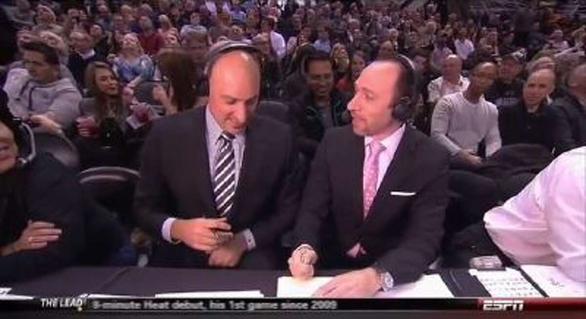ESPN broadcasters Jon Barry (left) and Dave Pasch flip a coin to see who has to interview Greg Popovich.