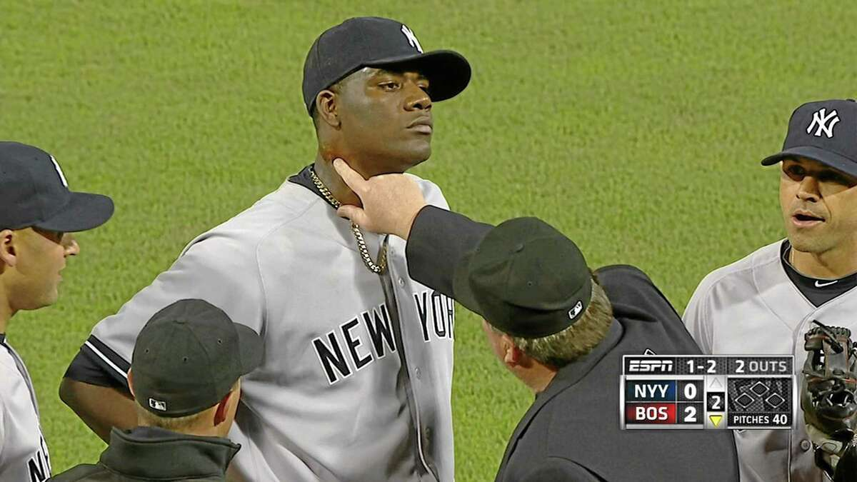 In this April 23 photo taken from video and provided by ESPN, home plate umpire Gerry Davis touches the neck of New York Yankees starting pitcher Michael Pineda, who was ejected after pine tar was found on his neck.