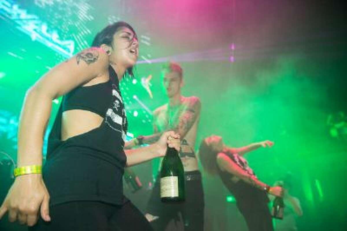 "Yasmine Yousaf, rapper Machine Gun Kelly and Jahan Yousaf perform at Krewella's ""Get Wet"" album release foam party at Exchange LA on September 24, 2013 in Los Angeles, California."