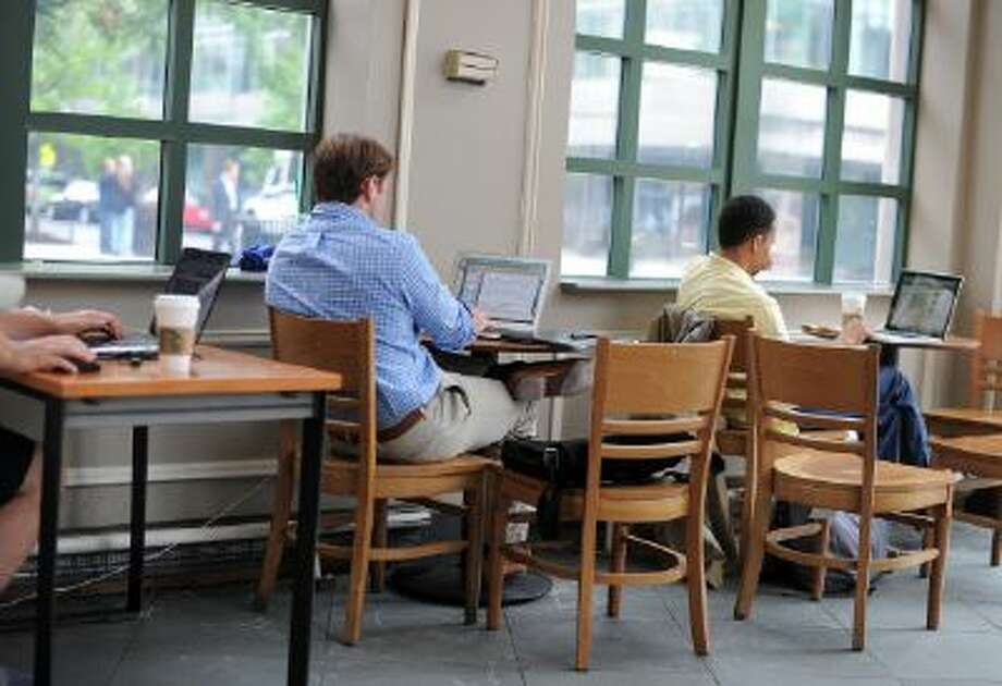 People use their laptop computers at a Starbucks in Washington, DC, on May 9, 2012.