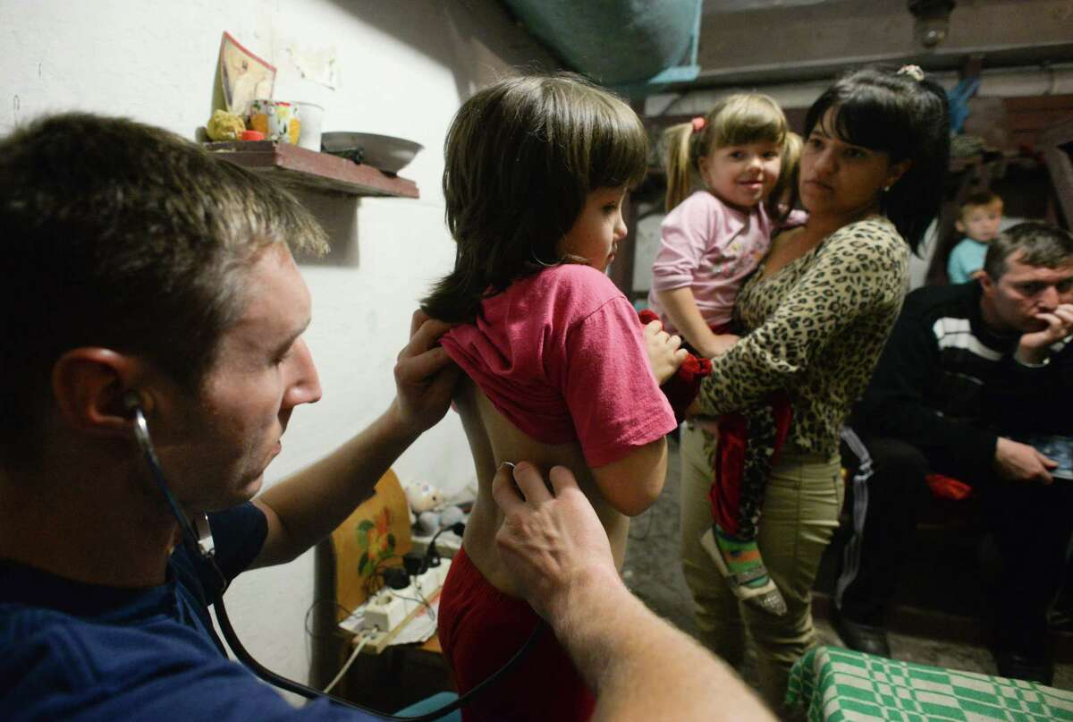 Alexey, volunteer doctor, examines children in bomb shelter in Petrovskiy district in Donetsk, eastern Ukraine, Monday, Sept. 1, 2014. The Petrovskiy district of Donetsk is currently a frontline and one of the districts which suffered the most from the artillery fights between Ukrainian army and Pro-Pussian rebels. (AP Photo/Mstislav Chernov)