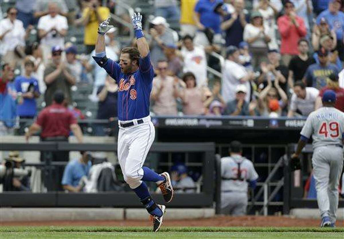 New York Mets Kirk Nieuwenhuis reacts running toward home plate after hitting a ninth-inning, walk-off, three-run, home run off Chicago Cubs relief pitcher Carlos Marmol, who leaves the field, far right, in a baseball game in New York, Sunday, June 16, 2013. (AP Photo/Kathy Willens)