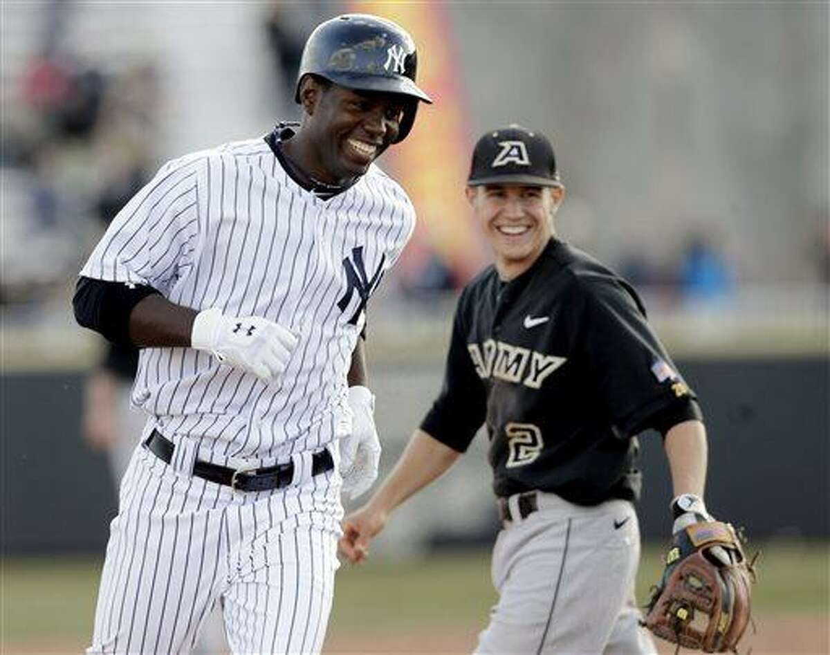 New York Yankees' Melky Mesa smiles as he passes Army third baseman Harold Earls after hitting a home run in the ninth inning of an exhibition baseball game at the United States Military Academy, Saturday, March 30, 2013, in West Point, N.Y. The Yankees won 10-5. (AP Photo/Mike Groll)