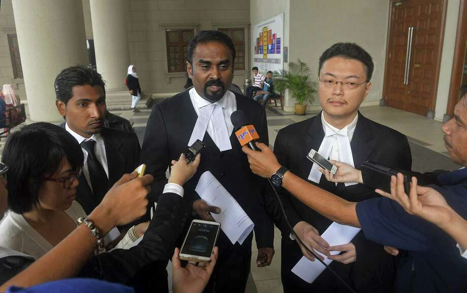 Malaysian lawyer Arunan Selvaraj, center, speaks to journalists outside a courthouse in Kuala Lumpur, Malaysia, Friday, Oct. 31, 2014. Two Malaysian teenage boys on Friday sued Malaysia Airlines and the government over the loss of their father on Flight 370, the first lawsuit filed by the family of a passenger of the jetliner that mysteriously disappeared eight months ago. (AP Photo) MALAYSIA OUT Photo: AP / AP