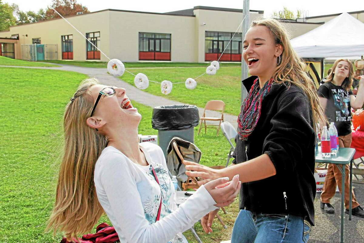 Torrington High School students participate in a donut-eating game during T-Fest on Saturday, Oct. 19.