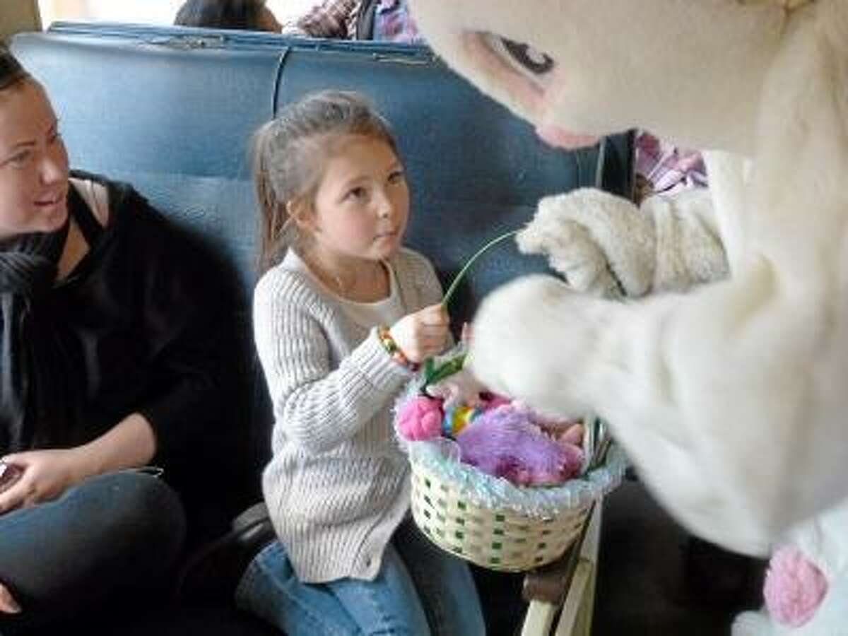 Ryan Flynn/Register Citizen A little girl attempts to take the Easter Bunny's entire basket on the Easter Bunny Express.