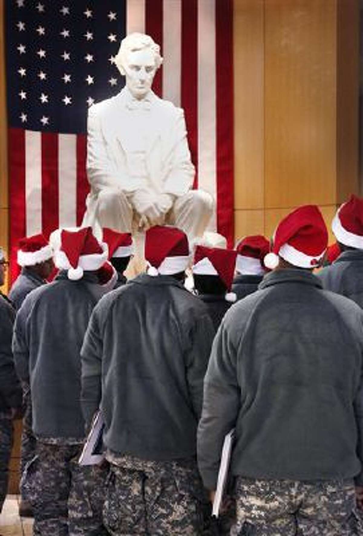 Wearing Santa hats instead of traditional military caps, a group of soldiers gather around a statue of Abraham Lincoln to hear a tour guide. Lincoln appears on the penny coin.