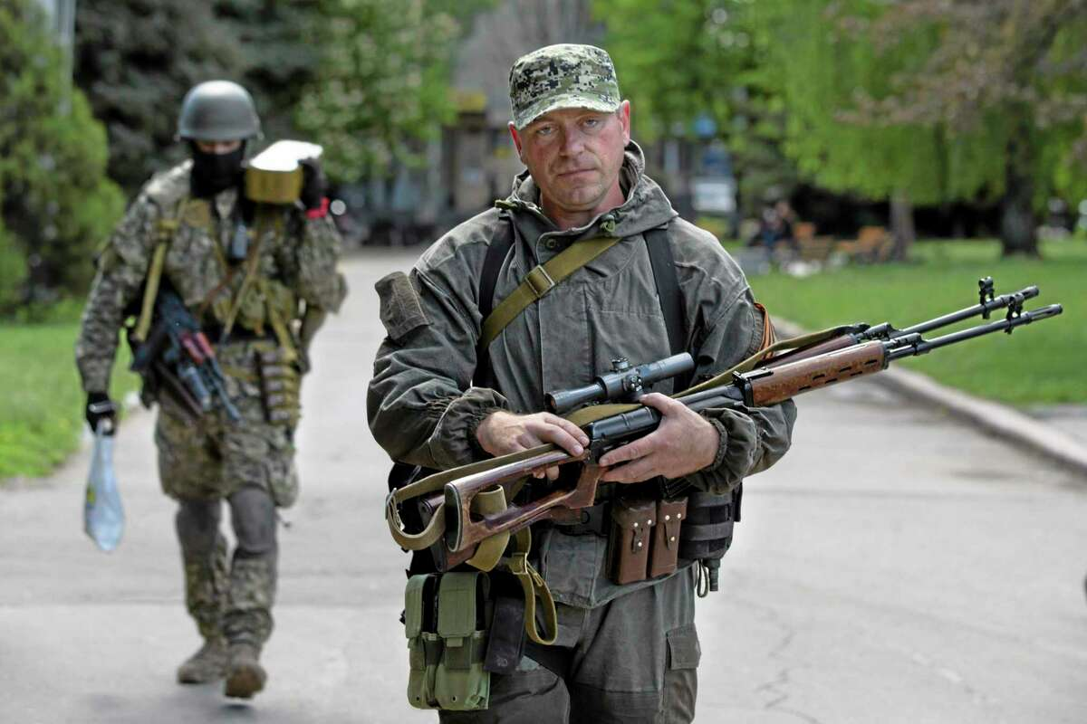 Pro-Russian gunmen carry their weapons at the local administration building in the center of Slovyansk, Ukraine, Tuesday, May 6, 2014. Thirty pro-Russia insurgents and four government troops have been killed during operations to expunge anti-government forces around Slovyansk, a key eastern city, Ukraine's interior minister reported Tuesday. (AP Photo/Alexander Zemlianichenko)